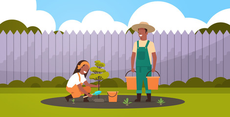 Printed kitchen splashbacks Purple couple farmers planting young tree african american man holding water buckets woman digging soil working in garden agricultural gardening concept backyard background full length horizontal
