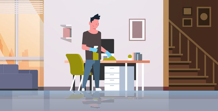 man cleaning computer table with duster guy wiping workplace desk housework concept modern living room interior male cartoon character full length horizontal