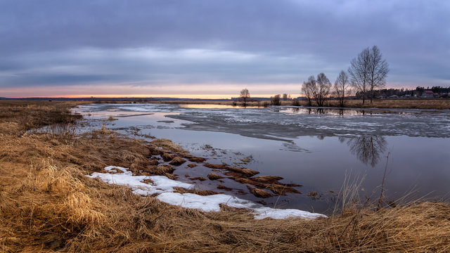 spring sunset panorama with trees on the river Bank and ice, Russia, Ural, April,