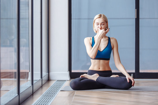 Charming slim woman yoga instructor doing padmasana basic yoga posture for pranayama in the spacious hall. The concept of breath control relaxation and meditation