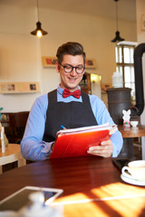 Portrait of young man sitting in his cafe and writing something while doing some paperwork