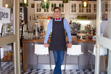 Confident young coffee shop owner man standing in cafe and waiting for guest