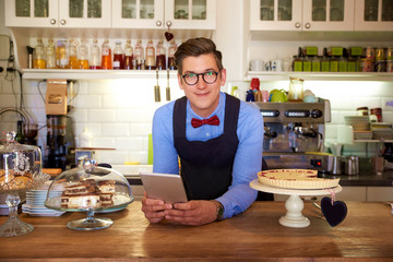 Young businessman standing in his cafe and waiting for guest while using digital tablet