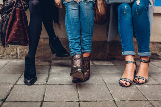 Three women wearing stylish shoes and accessories outdoors. Beauty fashion concept.