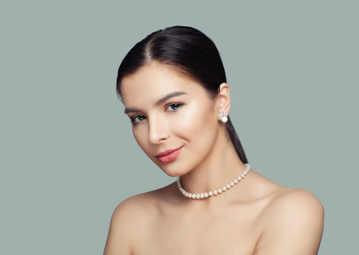 Beautiful woman with healthy skin wearing white pearls jewelry necklace