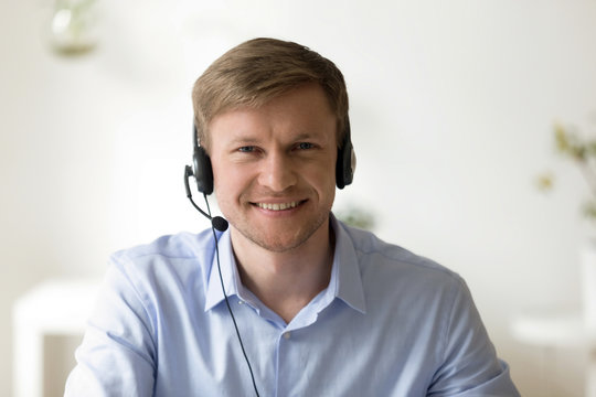 Portrait of handsome smiling man working in headphones at office