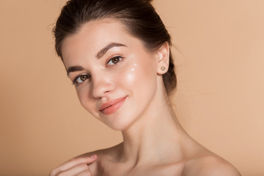 Beautiful face portrait of young woman with perfect skin with moisturizing face cream on a cheek. Skin care and health concept.