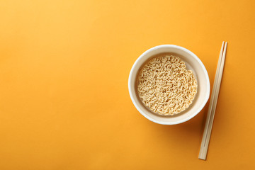 Cup of instant noodles with chopsticks on color background, top view. Space for text