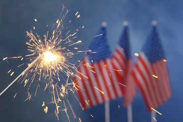 Burning sparkler against USA flags, closeup with space for text. Happy Independence Day