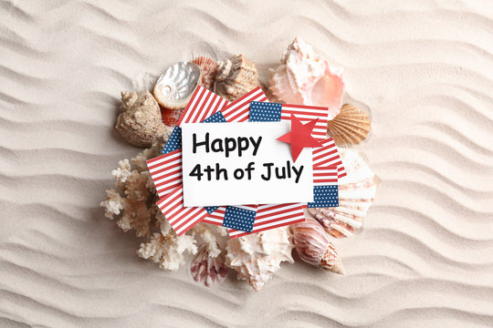Flat lay composition with greeting card, USA flags and seashells on sand. Happy Independence Day