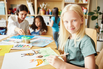 Adorable albino girl smiling and looking at camera while sitting at table and painting nice picture during lesson in art school