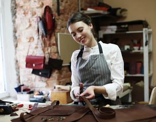 Fototapeta woman works in a bag making studio, cuts out details obraz
