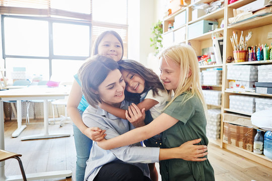Cute girls smiling and embracing tenderly their young teacher in classroom at art school