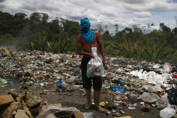Venezuelan Luis Ortega holds a bag of cans after scraping on a garbage dump in the border city of Pacaraima