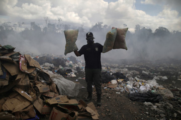 A Venezuelan man holds pillows after scraping on a garbage dump in the border city of Pacaraima
