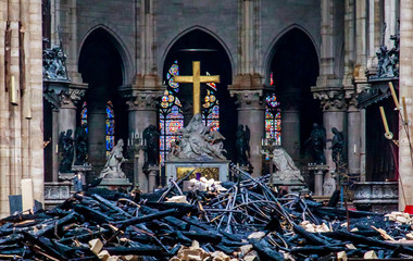 A view of the cross and sculpture of Pieta by Nicolas Coustou in the background of debris inside Notre-Dame de Paris, in the aftermath of a fire that devastated the cathedral, during the visit of French Interior Minister Christophe Castaner in Paris