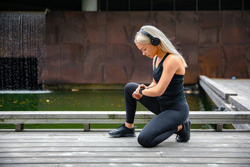 Sporty Female Runner Listening Music On Headphones and Using Smartwatch