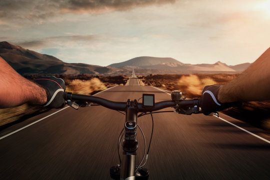 Riding a bicycle on an empty highway through the volcanic landscape with copy space
