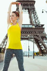 fit woman in sport clothes in Paris, France stretching