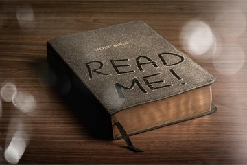 Holy Bible  book with read me letters on a wooden background