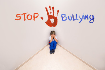 CHILD SUFFERING BULLYING, text over picture saying STOP BULLYING. Concept of child abuse or problems.