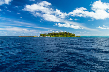 view from boat on sea ocean of tropical paradise maldives island resort with coral reef and turquoise blue ocean tourism blue sky background