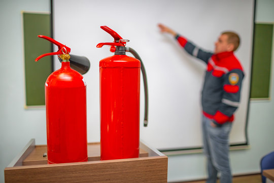 Uniformed fireman gives a lecture or instruction on fire safety. The instructor teaches the use of fire extinguisher