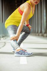 Closeup on sports woman on Pont de Bir-Hakeim bridge stretching
