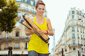 happy sports woman with 2 French baguettes crossing street