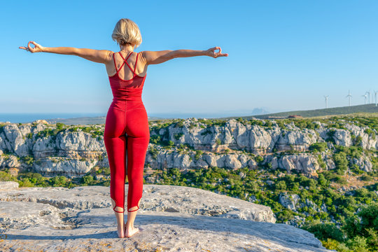 Yoga Fitness Woman Performing Angel Pose (Asana) with Chin Mudra Hands (Gesture of Consciousness). She is Standing at the Edge of Cliff Overlooking Mountain Range and Ocean in Far Distance.