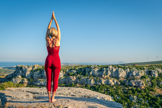 Yoga Fitness Woman Performing Mountain Pose (Tadasana). She is Standing at the Edge of Cliff Overlooking Mountain Range and Ocean in Far Distance.