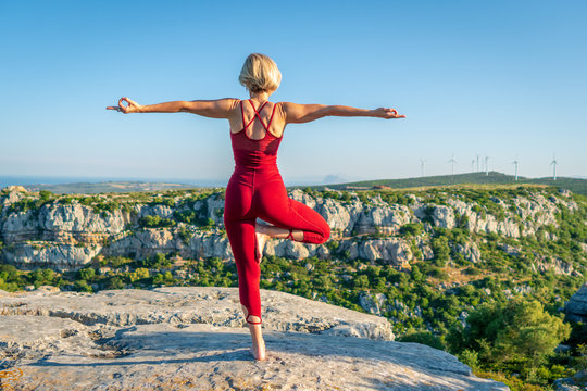 Yoga Fitness Woman Performing Tree Pose (Asana) with Chin Mudra Hands (Gesture of Consciousness). She is Standing at the Edge of Cliff Overlooking Mountain Range and Ocean in Far Distance.