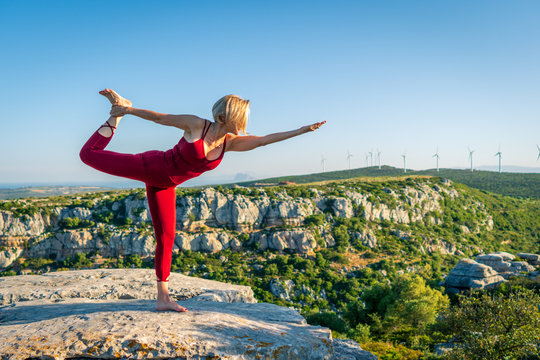 Yoga Fitness Woman Performing Lord of the Dance Pose (Natarajasana) with Bent Foot and Stretched Hand. She is Standing at the Edge of Cliff Overlooking Mountain Range and Ocean in Far Distance.