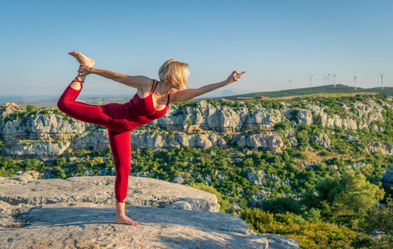 Yoga Fitness Woman Performing Lord of the Dance Pose (Natarajasana) with Chin Mudra Hand (Gesture of Consciousness) . She is Standing at the Edge of Cliff Overlooking Mountain Range and Ocean in Far.