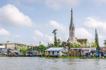 One of the banks of the Mekong river with the Cathedral of Cai Be, a river-land mixed town in Vietnam