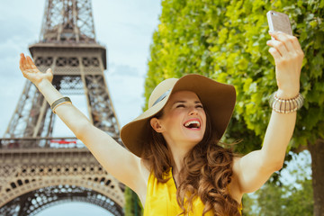 happy traveller woman rejoicing and taking selfie with phone