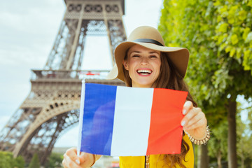 happy young solo traveller woman showing French flag
