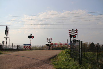 Railroad crossing with barriers and red lights with ICM koploper intercity train at Moordrecht in the Netherlands