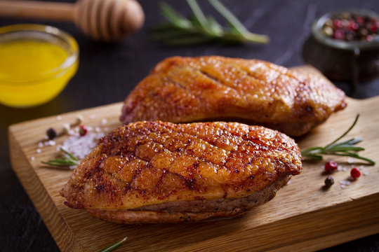 Roasted duck breast on chopping board - image