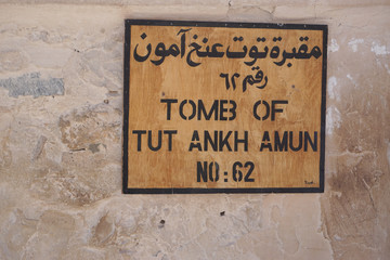 Luxor, Egypt: A plain wooden sign in Arabic and English indicates Tomb KV62, the burial place of pharaoh Tutankhamun, at the Valley of the Kings.