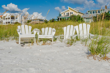 White Adirondack beach chairs on the white sand  on Pass-A-Grille's beach, St. Pete Beach, Florida