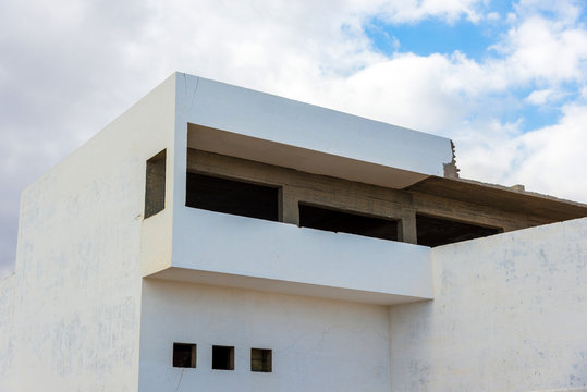 Part of a large white house against the sky