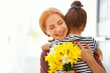 happy mother's day! child daughter   gives mother a bouquet of flowers to narcissus and gift.