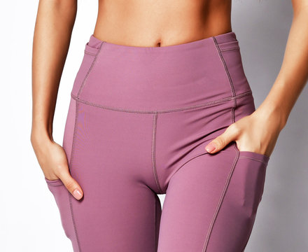 Closeup woman athletic body in sport wear pants on gray