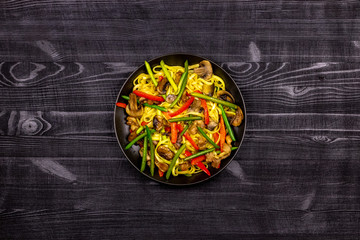 Appetizing stir fried noodles with garlic sprouts, mushrooms, red pepper and chicken meat on a black rustic background of a wooden table. A popular Asian dish