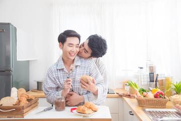 Young asian male homosexual couple wearing pajamas having beakfast in kitchen