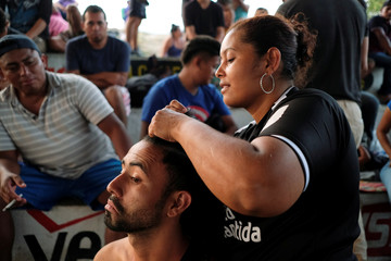 A woman from Honduras who braids for money works on a man's hair at an improvised shelter during a break in his journey towards the United States, in Huixtla