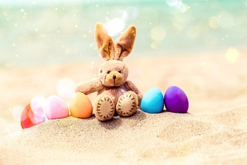 Easter bunny and color eggs on beach sand