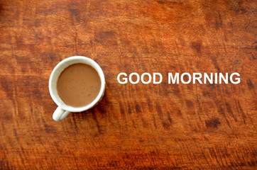 """Cup of drink with text """"Good morning"""" greeting."""