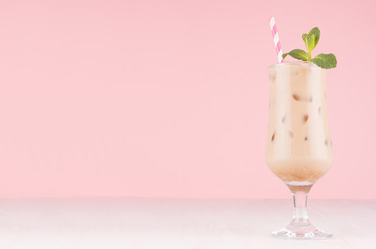 Coffee cold alcohol cocktail in goblet with green mint, ice cubes, straw in pastel light pink modern restaurant interior, copy space.